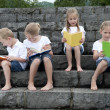Stock Photo: Summer holidays: children with book seated outdoors on stairs