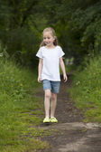 Summer holidays: Littel girl walking on a path in the woods — Stock Photo