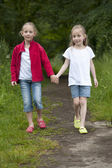 Summer holidays: Littel girls walking on a path in the woods — Stock Photo