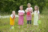 Cuatro niños jardinería con delantales — Foto de Stock