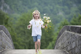 Little girl with daisies in her hair — Stock Photo