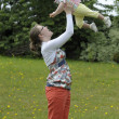 Stock Photo: Mother throwing her baby in the air,outdoors
