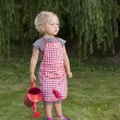 Little girl with watering can in the garden — Stock Photo