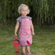 Stock Photo: Little girl with watering can in the garden