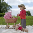 Little toddler playing with a pram outdoors — Stock Photo #31469347