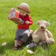 Little toddler seated in the garden with her teddy bear — Stock Photo