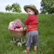 Little toddler playing with a pram outdoors — Stock Photo
