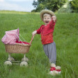 Little toddler playing with a pram outdoors — Stock Photo #31488333