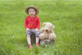 Piccolo bambino seduto in giardino con il suo orsacchiotto — Foto Stock