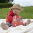 Toddler palying outdoors with memo cards — Stock Photo