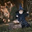 Little halloween witch outdoors in the woods — Stock Photo