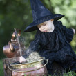 little halloween witch with couldron outdoors — Stock Photo