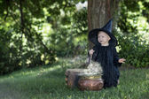 Little halloween witch outdoors with cauldron — Foto Stock
