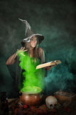 Halloween witch cooking a potion in a cauldron — Stock Photo
