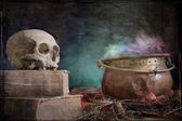 Old skull on old book and copper cauldron — Stock Photo
