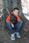 Boy seated against a tree — Stock Photo