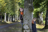 Two little girl looking from behind a tree — Stock Photo