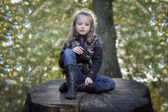 Girl seated on a trunk in the park — Stock Photo