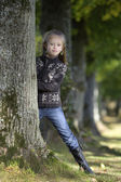 Little girl looking from behind a tree — Foto Stock