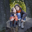 2 little girls sitting on a trunk  — Stock Photo