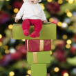 Little santa baby seated on presents — Stock fotografie