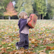 Little girl playing with a suitcase and autumn leaves — Stockfoto