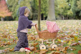 Little girl playing with a pram in the park — Stock Photo