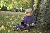 Little girl eating a biscuit , outdoors in the park — ストック写真