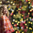 Little girl in front of a chrismas tree — ストック写真