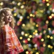 Little girl in front of a chrismas tree — Foto de Stock