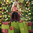 Little girl seated on christmas presents — Foto de Stock