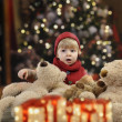 Little toddler with lots of teddy bears in front of a christmas tree — Stock fotografie