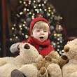 Little toddler with lots of teddy bears in front of a christmas tree — Stockfoto