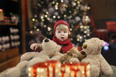 Little toddler with lots of teddy bears in front of a christmas tree — Stock Photo