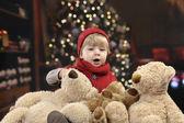 маленький малыш с большим количеством медвежат у елки — Стоковое фото