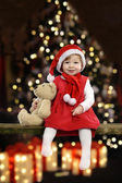 Little girl with christmas hat and teddy bear — Stock Photo