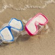 Summer time: Red and blue gogles on the sand washed by the ocean — Stock Photo