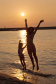 Lady and little girl jumping on the beach enjoying summer — Stock Photo