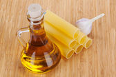 Cannelloni with olive oil in a glass bottle and garlic — ストック写真