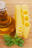 Cannelloni with olive oil in a glass bottle and fresh basil — Стоковое фото