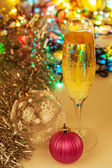 Glass of champagne and christmas decorations on new year backgro — Stock Photo
