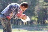 Pai segurando o filho pouco risonho — Fotografia Stock