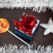 Blue gift box, candycane and white christmas star on black wood — Stock Photo #48816043