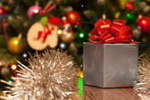 Gift box with red ribbon on festive Christmas background — Foto Stock