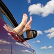 Woman legs out of car window — Stock Photo