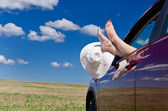 Legs out of car window — Stock Photo