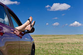 Woman legs in car window — Stock Photo