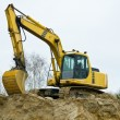 Yellow excavator on sandpit — Stock Photo