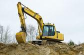Yellow excavator on sandpit — Stock Photo