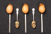 Chicken and quail eggs in spoons — Stock Photo